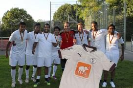 Die Spieler von Mahatma Hagen mit der Trophäe des Outdoor-Cups - und im Vordergrund das neue schicke Trikot mit Indien Aktuell Logo.