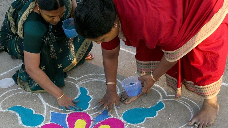 Frauen malen ein Rangoli vor ihre Haustür. Foto: Anne Roberts