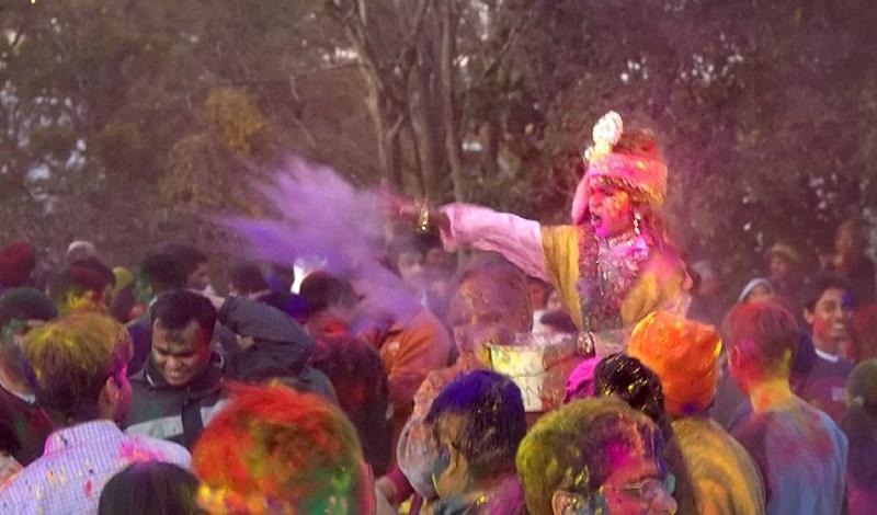 Ein kleiner als Krishna verkleideter Junge wirft Farbpulver in die Menge. Foto: JKP Barsana Dham