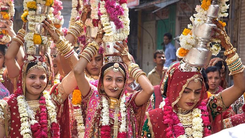 Reich geschmückte indische Frauen beim Gangaur Festival.