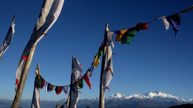 Gebetsfahnen in Sikkim, im Hintergrund die schneebedeckten Gipfel des Himalaya
